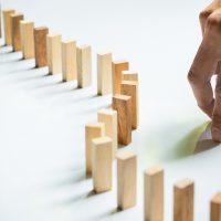 Bloco de madeira enfileirados imitando o efeito dominó. à direita mão imitando o caminhar com os dedos